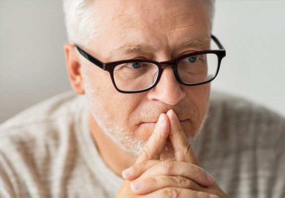 Man with glasses contemplating