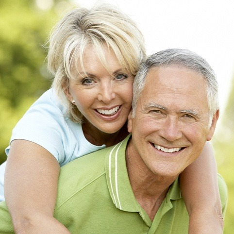 Older man and woman smiling outdoors after receiving periodontal services