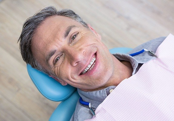 Smiling man in dental chair for non-surgical periodontal treatment