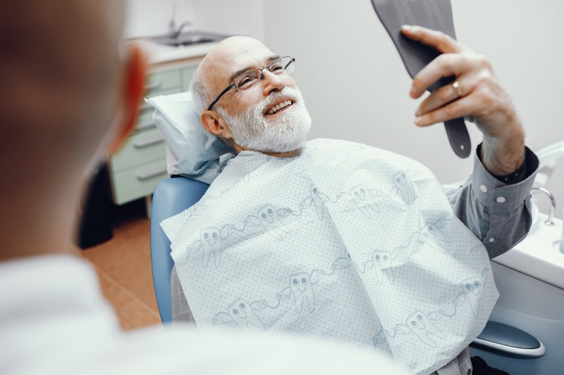 Man smiling in dental chair with dental implants